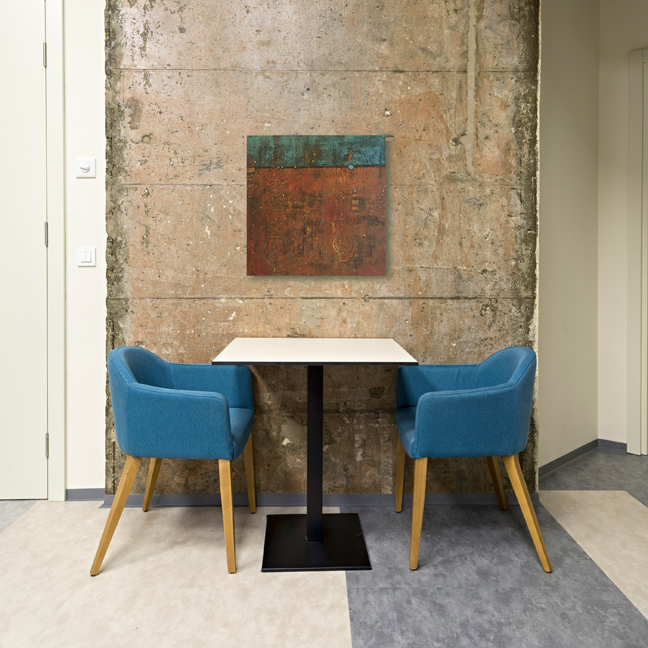 Blue chairs and table in front of a concrete wall